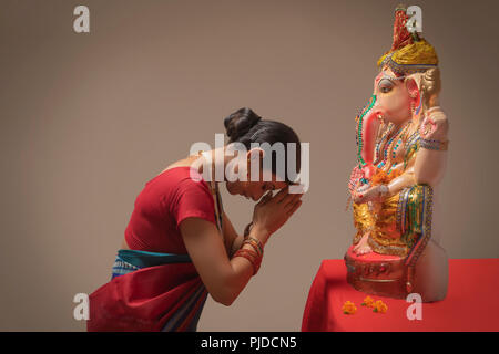 Woman praying with hands joined and eyes closed in front of Ganpati Idol. - Stock Photo
