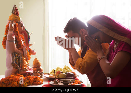 Husband and wife praying with hands joined in front of Ganesha Idol on the occasion of Ganesh Chaturthi - Stock Photo