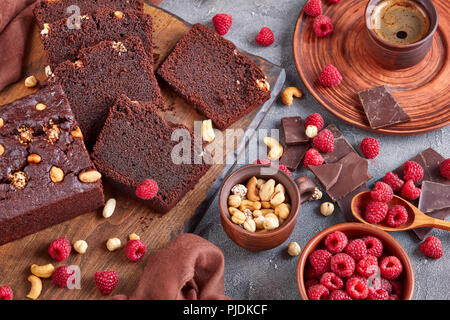 close-up of chocolate buckwheat pound cake with nuts and raspberries cut in slices on a wooden board on a concrete table with cup of coffee and brown  - Stock Photo