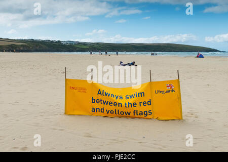 A RNLI safety advice banner on Crantock beach in Newquay Cornwall. - Stock Photo