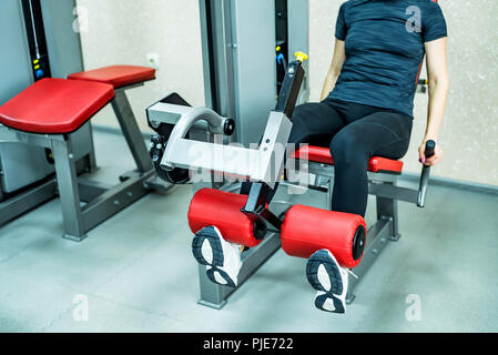 Young woman does leg exercises in gym - Stock Photo