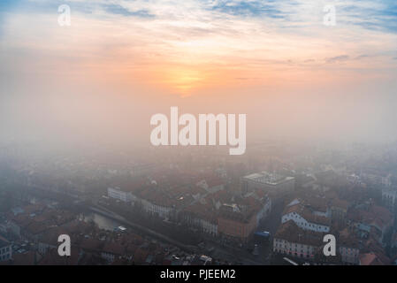 Colorful winter sunset through the mist over the Ljubljana city, capital of Slovenia, aerial view, on a cold day of December. - Stock Photo