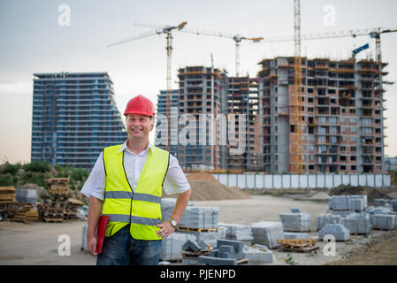 Engineer looking at camera on a construction site wearing reflective west working on housing project - Stock Photo