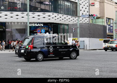 Toyota JPN Taxi with Tokyo Olympic logo on it going through a junction in Ginza in front of the Ginza Place building. Slight motion blur. August 2018 - Stock Photo