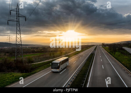 Bus traveling on a lonely countryside Highway with the sunset behind - Stock Photo