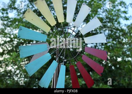 colorful garden windmill with a tree in the background - Stock Photo