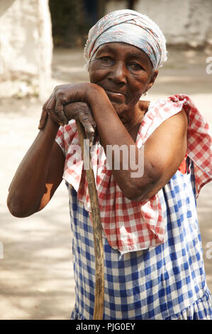 An elderly Haitian woman leans agains her broom, pausing from her daily task of sweeping to gaze at the camera in Gonaives, Haiti. - Stock Photo