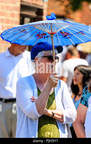 Senior woman, caucasian, standing in bright sunlight, she wears baseball cap and white cardigan and holds Japanese style blue paper parasol. - Stock Photo