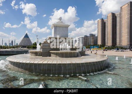 Astana, Kazakhstan, August 3 2018: Fountain on Independence Square with Palace of Peace and Reconciliation in the background - Stock Photo