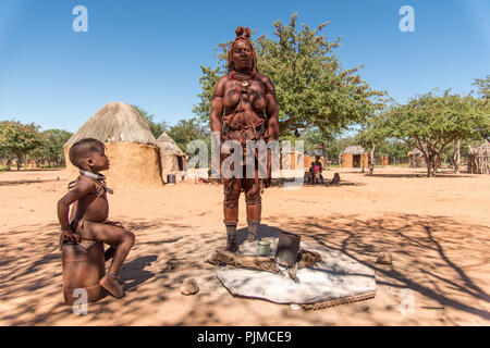 Himba girl and Himba woman at a fire pit in a Himba village in Namibia - Stock Photo