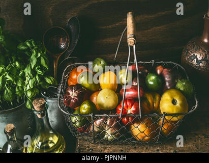 Colorful organic tomatoes in harvest basket on dark rustic kitchen table with cooking ingredients. Healthy food concept - Stock Photo