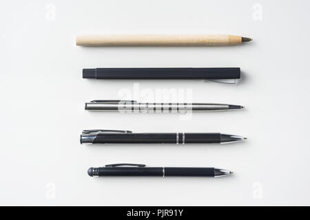 Top view of collection of pens on white background desk for mockup - Stock Photo