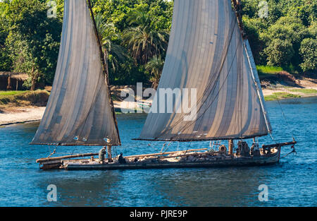 Traditional working sailing ship with old sails with holes transporting large stones with Egyptian men in traditional robes, Nile River, Egypt, Africa - Stock Photo