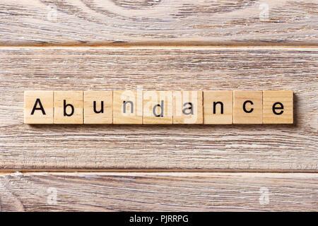 abundance word written on wood block. abundance text on table, concept. - Stock Photo