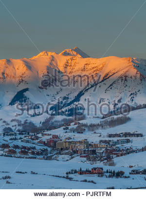 Sunset light called alpenglow shines on Whiterock Mountain towering over the town of Mount Crested Butte, Colorado, home of Crested Butte Mountain Res - Stock Photo