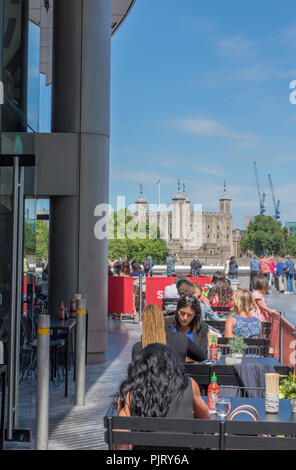 diners and people eating on the terrace outside of a restaurant at more london riverside in central london with the tower of london in the distance. - Stock Photo