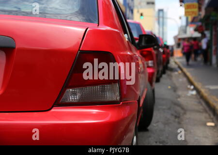 Red taxis queued in traffic, San Jose, Costa Rica - Stock Photo