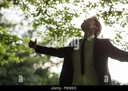 Young peaceful businessman standing in spring forest looking upwards towards the sky with his arms open wide and thumbs up. - Stock Photo