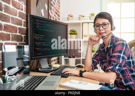 young pretty programmer wearing head phone and looking to screen with a confident smile - Stock Photo