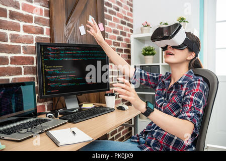 young female touching air by wearing virtual reality goggles in a future technology way. - Stock Photo