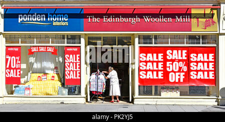 Old lady shopping at clothes rail in entrance Edinburgh Wool Mill high street retail clothing store sale posters shop front window Brentwood Essex UK - Stock Photo