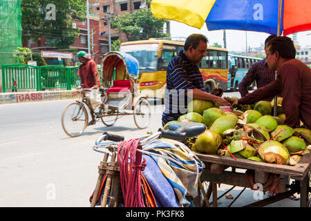 A street vendor selling fresh coconuts as a cycle rickshaw passes in the background on the street in Dhaka, Bangladesh. - Stock Photo