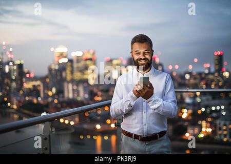 A businessman with smartphone standing against night London view panorama. - Stock Photo