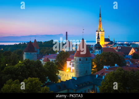 Tallinn city, view at night of the medieval Lower Town quarter with St Olaf's Church illuminated in the distance, Tallinn, Estonia. - Stock Photo