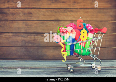 Shopping cart with items for birthday celebration on wooden background. Toned image. - Stock Photo
