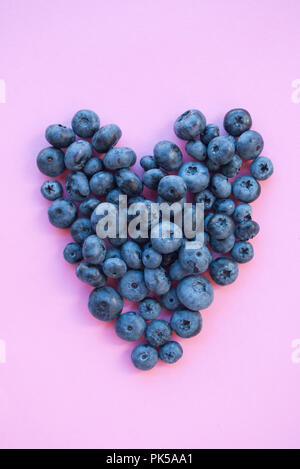 Delicious freshly picked bluberry in a form of heart on pink background. Healthy food concept. - Stock Photo