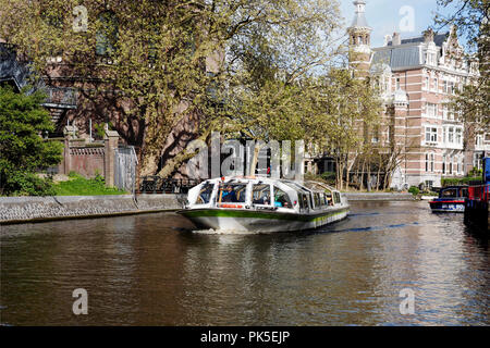 Amsterdam canal scene with large tour boats on the main canal by Stadhouderskade. These boats provide trips along the canals and harbour for tourists. - Stock Photo