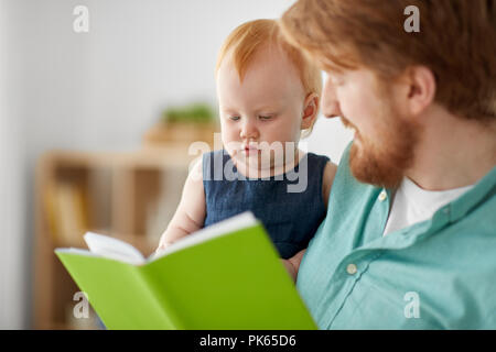 father and baby daughter with book at home - Stock Photo