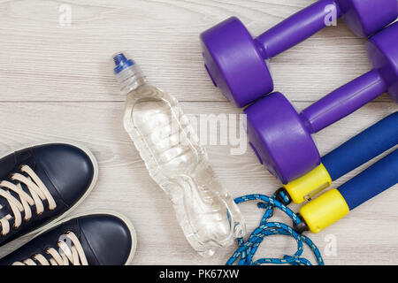 Different tools for fitness with bottle of water in room or gym on grey floor - Stock Photo
