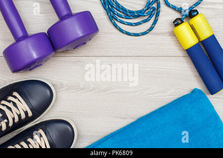 Different tools for fitness in room or gym on grey floor - Stock Photo