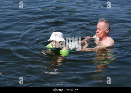 A four year old girl learning to swim with her grandfather - Stock Photo