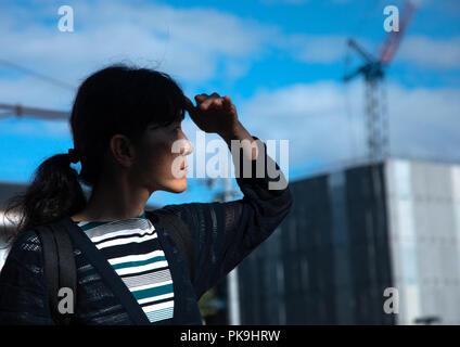 Japanese woman looking away and blocking sun with hand, Kansai region, Kyoto, Japan - Stock Photo