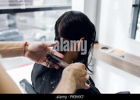 Man's hands cut and comb female dark brown hair in a beauty salon with mirrors - Stock Photo