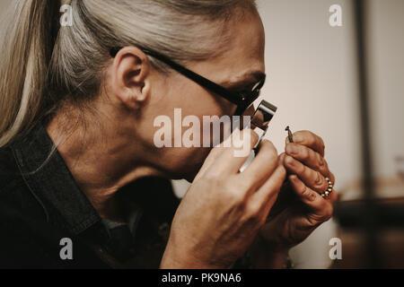 Close up of woman jeweler examining diamond through loupe at workshop. close-up Senior female jeweler looking at diamond through magnifying loupe. - Stock Photo