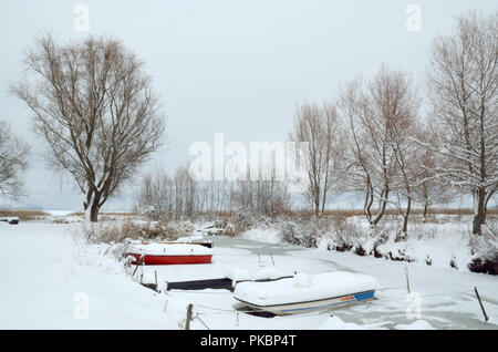 Small fishing boats covered with snow - Stock Photo
