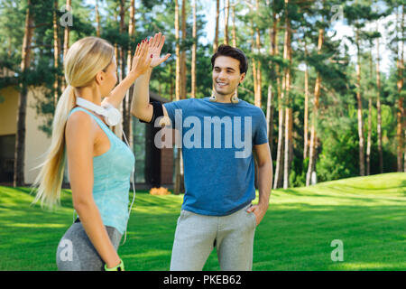 Joyful positive people giving each other high five - Stock Photo