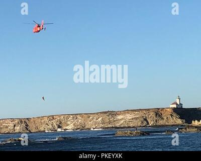 A Coast Guard aircrew aboard an MH-65 Dolphin helicopter airlifts a stranded kayaker off a rock near Qochyax Island at Sunset Bay State Park, Ore., August 3, 2018.    The 44-year-old kayaker capsized his kayak and swam to the rocks and waved down help with his paddle. - Stock Photo
