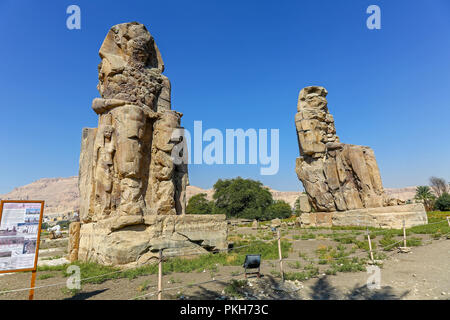 The Colossi of Memnon, two massive stone statues of the Pharaoh Amenhotep III, at the Theban Necropolis at Luxor, Egypt, Africa - Stock Photo