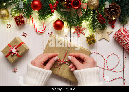 Woman's hands tying up christmas gift box on white wooden table with festive ornaments and lights - Stock Photo