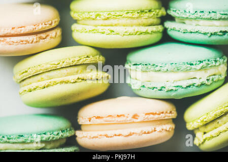 Pastel colored French macaroons cookies over light background - Stock Photo