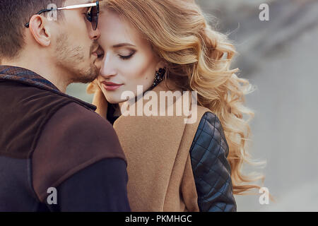 Beautiful couple in love on Valentine's Day. Happy young couple walking on the sandy mountains on a cloudy day - Stock Photo