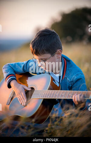 A little boy with glasses sitting in the field and enthusiastically playing the guitar. Nature, beauty. - Stock Photo