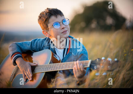 A little boy with glasses playing guitar in the field. Nature, beauty. - Stock Photo