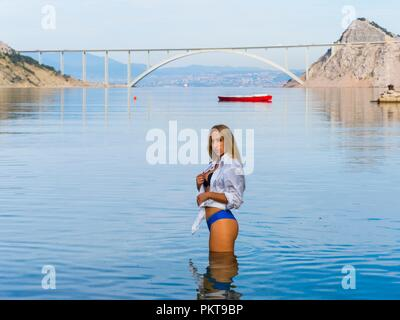Long haired blonde pretty teen girl in calm sea before bridge in background serious looking at camera alone single solo female - Stock Photo
