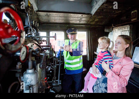 15 September 2018, Berlin: Visitors to the 15th Berlin Railway Festival look at the driver's cab of a steam locomotive in the Schöneweide depot. Steam trains are the focus of the two-day event. The association Dampflokfreunde Berlin presents more than 20 locomotives and wagons. Photo: Christoph Soeder/dpa - Stock Photo