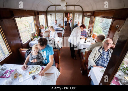 15 September 2018, Berlin: At the 15th Berlin Railway Festival, visitors sit in the dining car of a train in the Schöneweide depot. Steam trains are the focus of the two-day event. The association Dampflokfreunde Berlin presents more than 20 locomotives and wagons. Photo: Christoph Soeder/dpa - Stock Photo